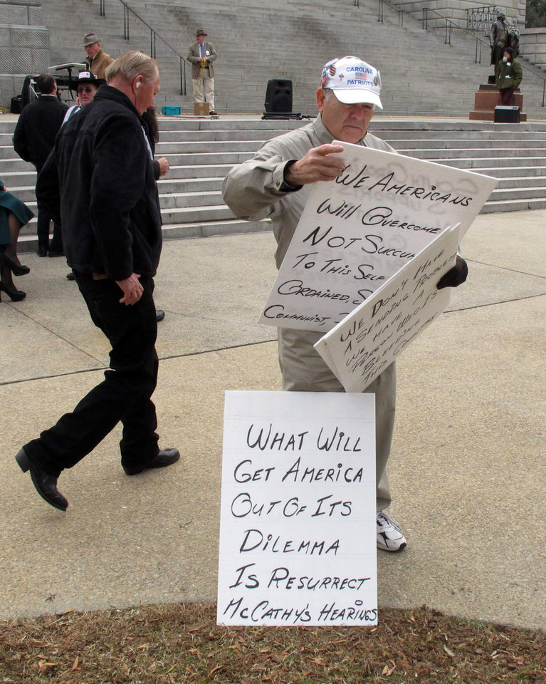 In this Tuesday, Jan. 8, 2013 photo, Dick LoBue looks through his signs at a rally to support a bill to nullify the new health care law supported by President Barack Obama in Columbia, S.C. The bill is one of several pieces of legislation in South Carolina designed to go around federal laws. (AP Photo/Jeffrey Collins)