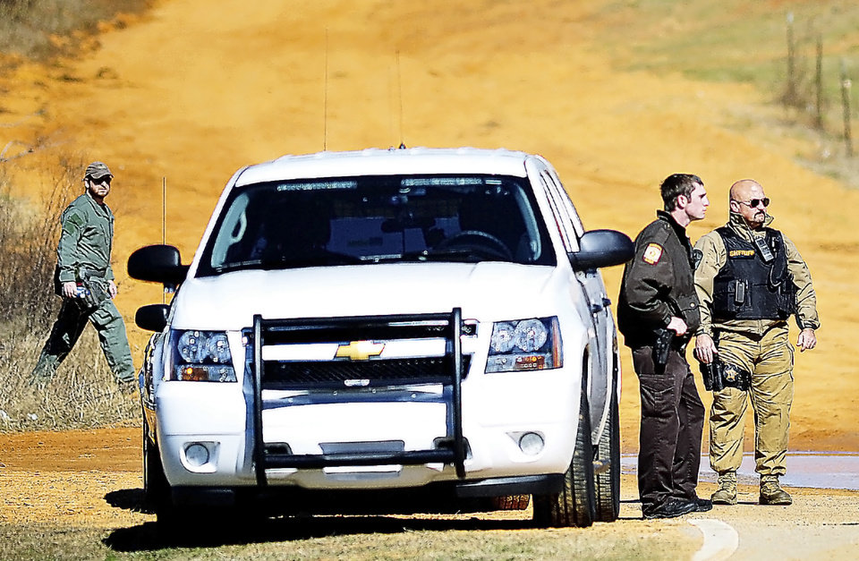 Photo - Authorities work a check point, Wednesday, Jan. 31, 2013, in Midland City, Ala., below the home where Tuesday's school bus shooting suspect is barricaded in a bunker with a five-year-old boy as hostage. Speaking into a 4-inch-wide ventilation pipe, hostage negotiators tried Thursday to talk a man into releasing a kindergartener and ending a standoff in an underground bunker that stretched into its third day. (AP Photo/Dothan Eagle, Jay Hare)