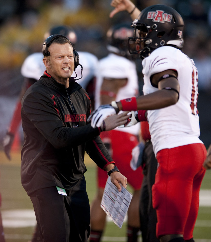 Photo - FILE - In this Sept. 28, 2013 file photo, Arkansas State head coach Bryan Harsin, left, encourages his player Phillip Butterfield, right, during the second quarter of an NCAA college football game against Missouri in Columbia, Mo. A person familiar with the decision tells The Associated Press that Boise State has hired  Harsin as its next coach. The person spoke on condition of anonymity because the move had not become official. (AP Photo/L.G. Patterson, File)
