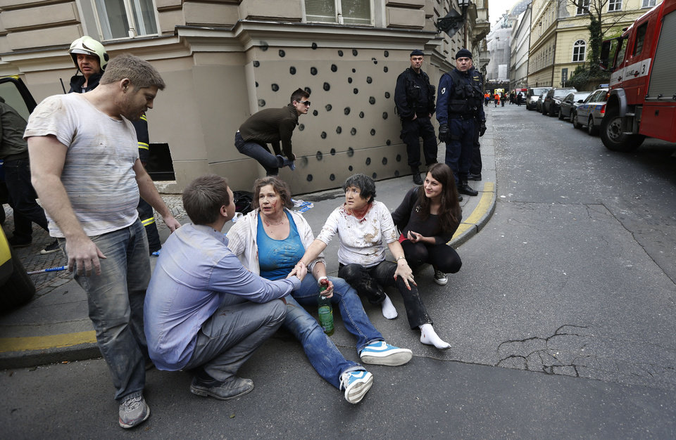 Photo - Injured people sit on a sidewalk after a explosion downtown Prague, Czech Republic, Monday, April 29, 2013. Police said a powerful explosion has damaged a building in the centre of the Czech capital and they believe some people are buried in the rubble. (AP Photo/Petr David Josek)