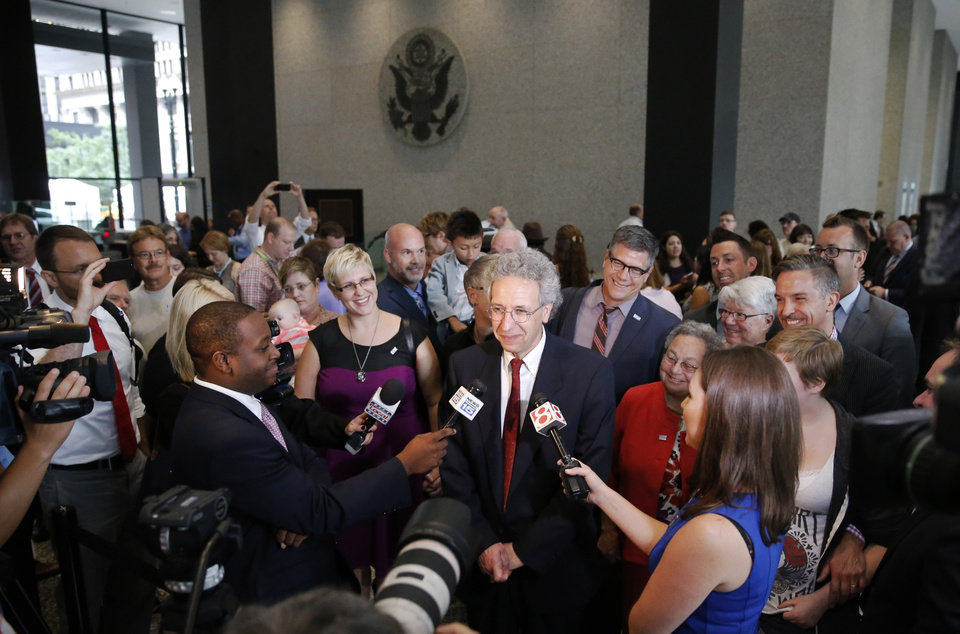 Photo - ACLU attorney Ken Faulk, center, talks to reporters surrounded by plaintiffs and supporters of gay marriage, after Faulk participated in a hearing before the 7th U.S. Circuit Court of Appeals on the challenges to Indiana and Wisconsin's gay marriage ban Tuesday, Aug. 26, 2014, in Chicago. (AP Photo/Charles Rex Arbogast)
