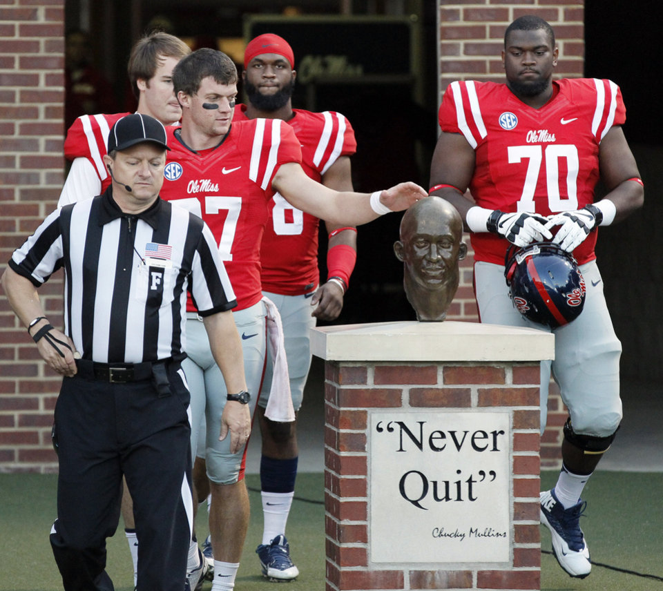 Photo - In this photo taken on Oct. 19, 2013, Mississippi players, including Emmanuel McCray (70), touch the bust of former defensive back Roy Lee