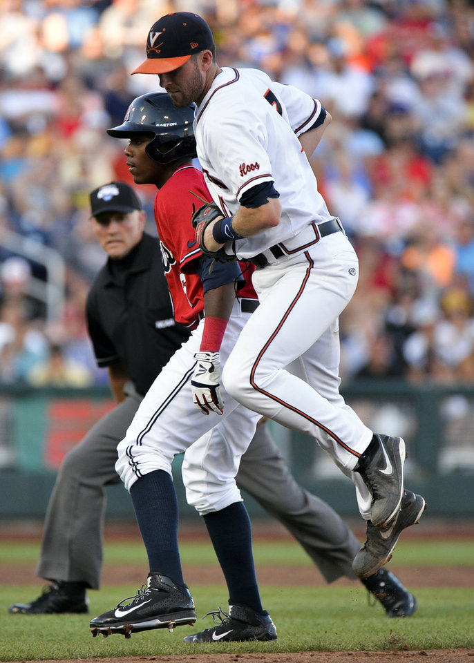 Photo - Mississippi's Errol Robinson is tagged out by Virginia second baseman Branden Cogswell, right, after he was caught in a run down between first and second bases, in the third inning of an NCAA baseball College World Series game in Omaha, Neb., Sunday, June 15, 2014. (AP Photo/Ted Kirk)