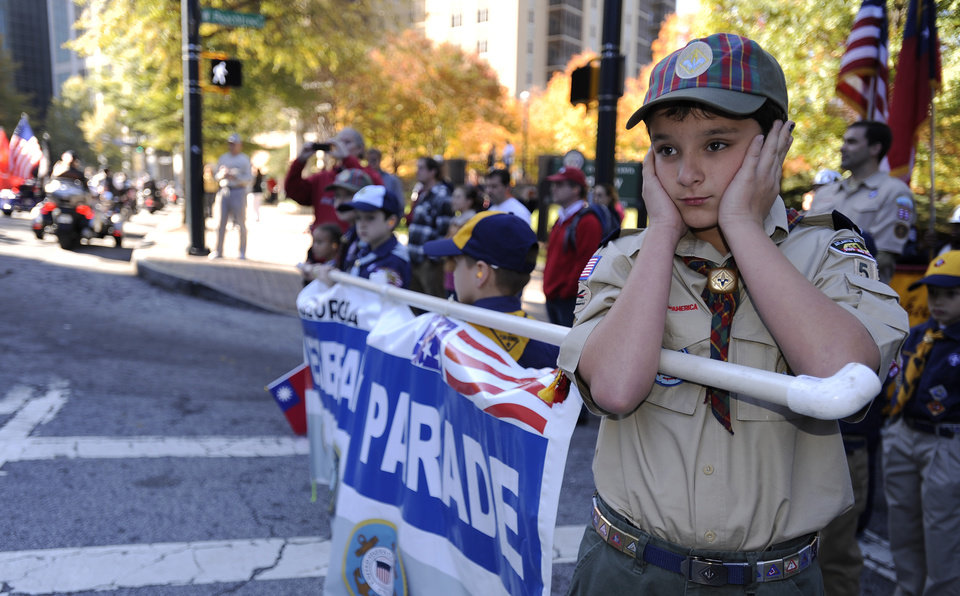 Cub Scout Ethan Jennings covers his ears as motorcycles roar by to start the 31st annual Veterans Day Parade through downtown Atlanta, Saturday, Nov. 10, 2012. (AP Photo/David Tulis)