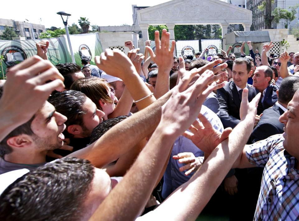 Photo - This photo released on the official Facebook page of Syrian President Bashar Assad, shows Syrian president Bashar Assad, right, surrounded by bodyguards as young people, wave at him during the inauguration ceremony on Saturday of a statue dedicated to