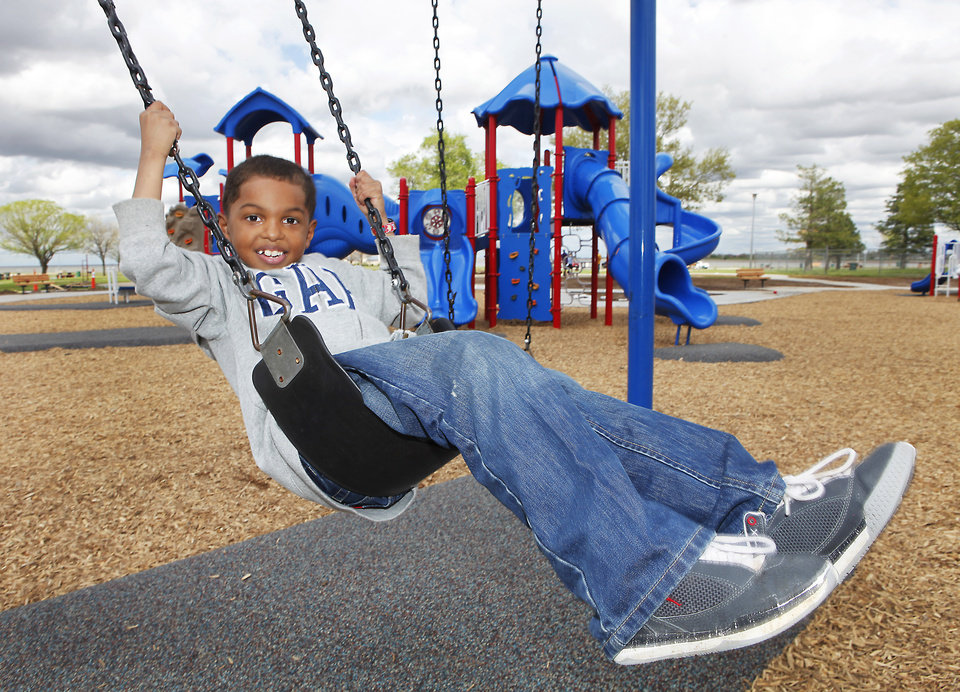 Sherwin Scott, on his seventh birthday, swings on the new playground at Stars and Strips park on Lake Hefner. Art for story on Oklahoma City parks long-term plan story, Tuesday, March 19, 2012.  Photo By David McDaniel/The Oklahoman