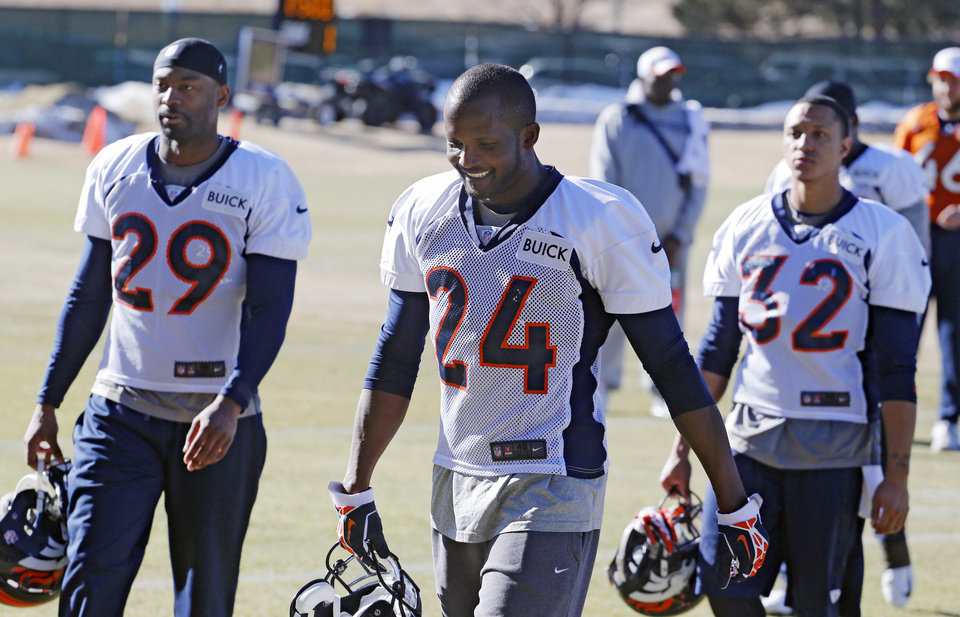 Photo - FILE - In this Jan. 17, 2014 file photo, Denver Broncos cornerback Champ Bailey (24) walks off the field free safety Michael Huff (29) and cornerback Tony Carter (32) after NFL football practice at the team's training facility in Englewood, Colo. The Broncos are scheduled to play the Seattle Seahawks in the NFL Super Bowl on Feb. 2, in East Ruterford, N.J. It will be Bailey's first Super Bowl. (AP Photo/Ed Andrieski, File)