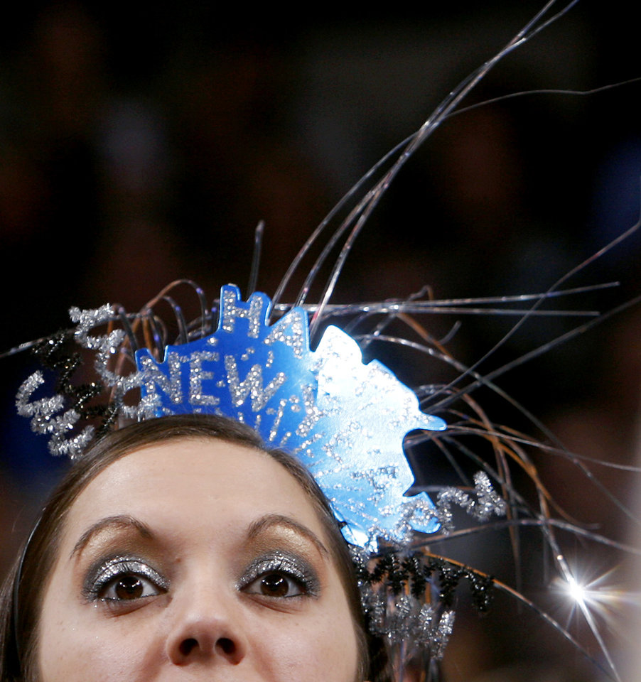 Photo - Dressed in a New Year's Eve tiara, Oklahoma City fan Nauzi Jagosh watches the Thunder play Atlanta during their NBA basketball game at the OKC Arena in Oklahoma City on Friday, Dec. 31, 2010. Photo by John Clanton, The Oklahoman