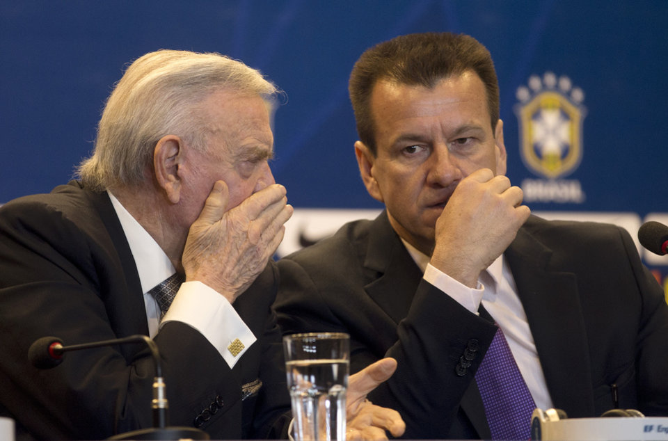 Photo - Brazil's soccer coach Dunga, right, listens to Brazilian Football Confederation Presdident Jose Maria Marin during a press conference in Rio de Janeiro, Brazil, Tuesday, Aug. 19, 2014. Dunga summoned players for upcoming friendly games against Colombia and Ecuador, the first time he picked players since taking over the national team from Luiz Felipe Scolari after the World Cup. (AP Photo/Silvia Izquierdo)