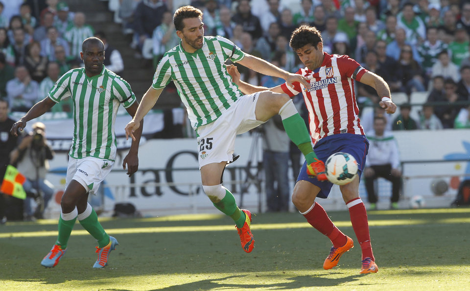 Photo - Atletico de Madrid's Diego Costa, right, and Betis'  Jordi Figueras , centre, fight for the ball as Betis' Paulao Santos, right, looks on during their La Liga soccer match at the Benito Villamarin stadium, in Seville, Spain on Sunday, March 23, 2014. (AP Photo/Angel Fernandez)