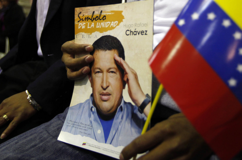 "A man holds a picture of Venezuela's President Hugo Chavez and a Venezuelan flag during a Mass to pray for the leader on what was supposed to be his inauguration day, at a church in La Paz, Bolivia, Thursday, Jan. 10, 2013.  Chavez has been fighting an unspecified type of pelvic cancer since June 2011 and has undergone repeated surgeries, chemotherapy and radiation treatments. Venezuela's government said in its last update on Monday that Chavez was in a ""stable situation"" while being treated for a severe respiratory infection. The government has hasn't said how severe his ""respiratory deficiency"" is. (AP Photo/Juan Karita)"