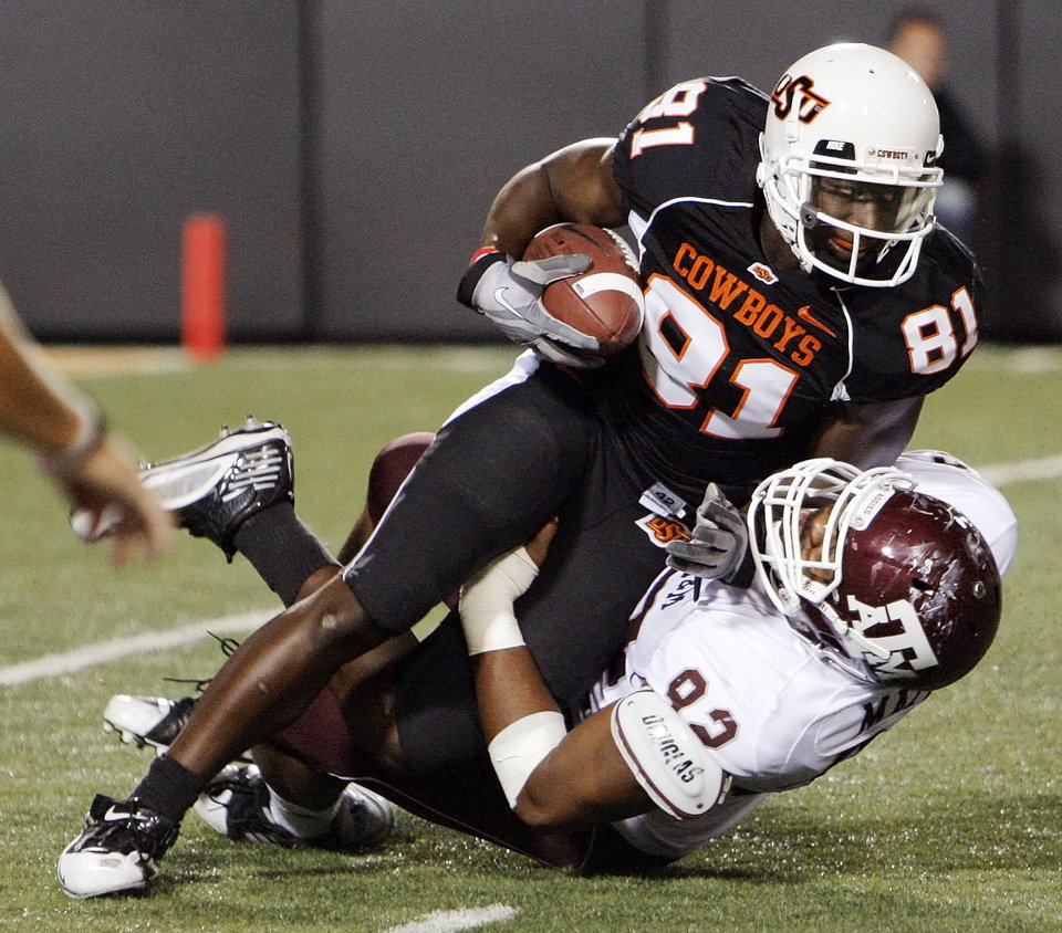 Photo - OSU's Justin Blackmon (81) is dropped for a loss by Jonathan Mathis (92) of Texas A&M in the first quarter during the college football game between Texas A&M University and Oklahoma State University (OSU) at Boone Pickens Stadium in Stillwater, Okla., Thursday, Sept. 30, 2010. Photo by Nate Billings, The Oklahoman