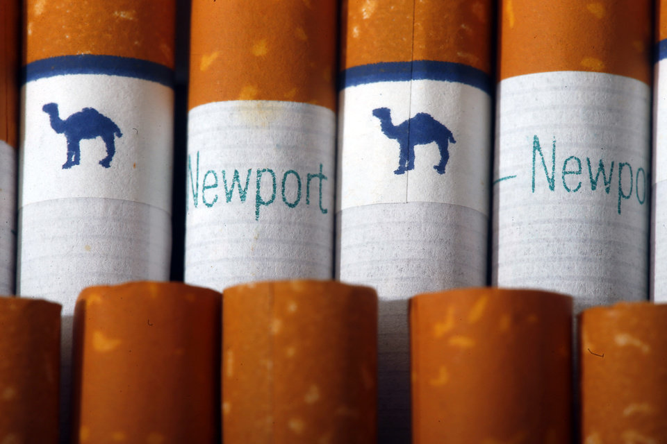 Photo - Camel, a Reynolds American brand, and Newport, a Lorillard brand, cigarettes are arranged for a photo Tuesday, July 15, 2014 in Philadelphia. Reynolds American Inc. is planning to buy rival Lorillard Inc. for about $25 billion in a deal to combine two of the nation's oldest and biggest tobacco companies, the companies announced Tuesday. (AP Photo/Matt Rourke)
