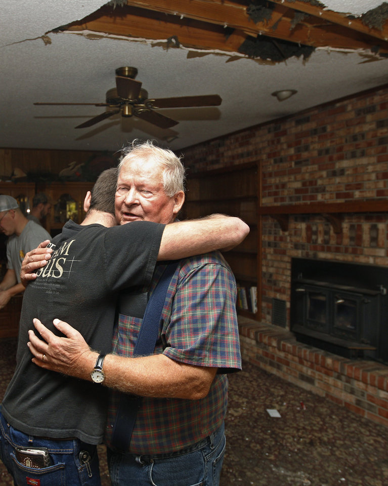 Joe Reneau, right, gets a hug from friend Cody Parsons, in his family room in Sparks, Okla., Sunday, Nov. 6, 2011. The room was damaged when the chimney collapsed during an earthquake and fell partially through the roof, at upper right. Neither Joe nor his wife, Mary, were in the room at the time, and were not injured. (AP Photo/Sue Ogrocki) ORG XMIT: OKSO104
