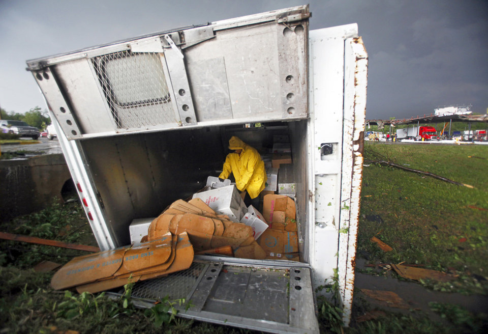 A Frito-Lay driver looks through his inventory in his turned over delivery truck after a tornado damaged the area Monday around Interstate 40 and Choctaw Road in Oklahoma City. Photo by Chris Landsberger, The Oklahoman