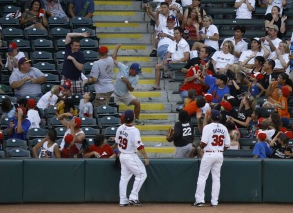Photo - A foul ball flies into the stands during a game between the Oklahoma City RedHawks and the Omaha Storm Chasers in Oklahoma City, Saturday, June 23, 2012. Photo by Garett Fisbeck, The Oklahoman