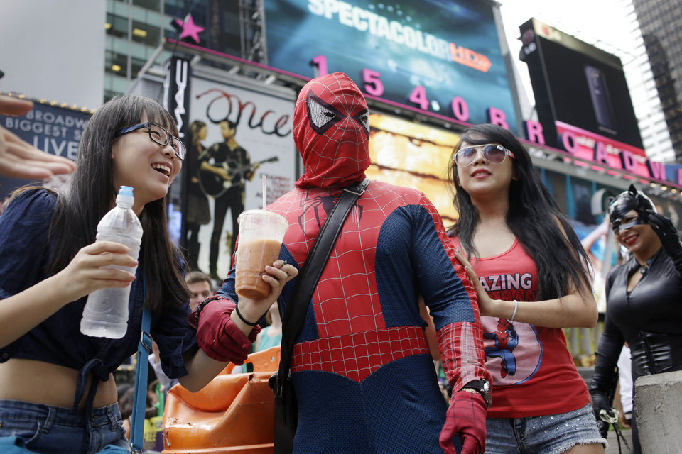 "Photo - New York City Mayor Bill de Blasio said Monday, July 28, 2014 that he believes the people wearing character costumes in Times Square should be licensed and regulated. Dozens of people dressed as kids' favorites like Elmo, Cookie Monster and Batman stand near 42nd Street and pose for photos with tourists in exchange for money. De Blasio said the practice has ""gone too far.""  A man dressed as Spider-man was arrested Saturday, July 28, 2014, after punching a police officer who told him to stop harassing tourists.  The City Council is working on legislation that would require the characters to get a city-approved license.  (AP Photo/Seth Wenig)"
