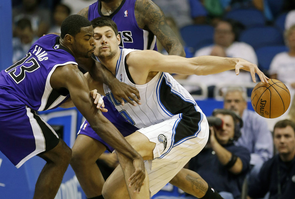 Sacramento Kings' Tyreke Evans (13) tries for a steal as Orlando Magic's Nikola Vucevic, of Montenegro, works to keep control of the ball during the first half of an NBA basketball game, Wednesday, Feb. 27, 2013, in Orlando, Fla. (AP Photo/John Raoux)