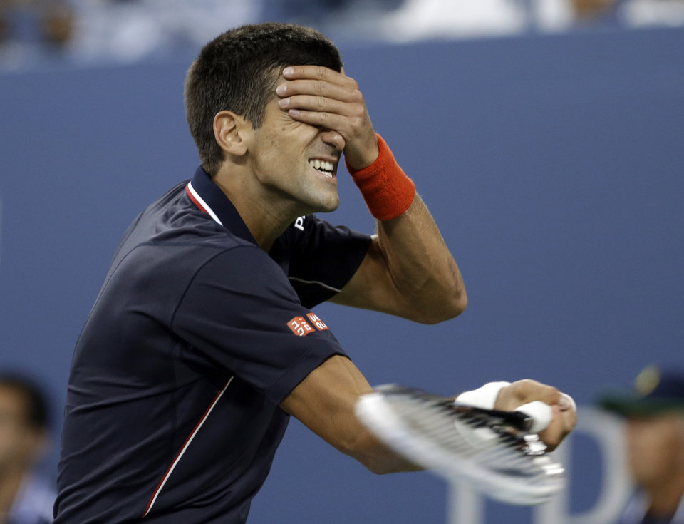 Photo - Novak Djokovic, of Serbia, reacts after missing a return to Andy Murray, of Britain, during the quarterfinals of the U.S. Open tennis tournament Thursday, Sept. 4, 2014, in New York. (AP Photo/Darron Cummings)