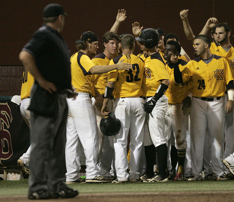 Photo - Kennesaw State's Bo Way, number 32, is congratulated by teammates after scoring  against Georgia Southern in the eleventh inning of an NCAA regional college baseball game on Saturday,  May 31, 2014, in Tallahassee, Fla. Kennesaw scored 8 runs in the eleventh to win the game 13-5.   (AP Photo/Steve Cannon)