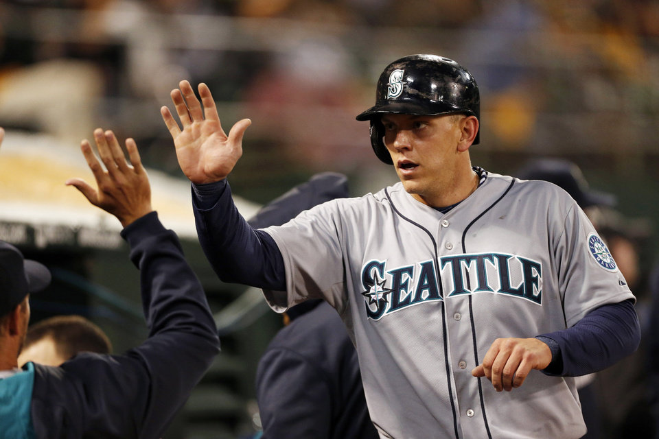 Photo - Seattle Mariners' Kyle Seager is congratulated after scoring a run during the fifth inning of a baseball game against the Oakland Athletics, Thursday, April 3, 2014, in Oakland, Calif. (AP Photo/Beck Diefenbach)