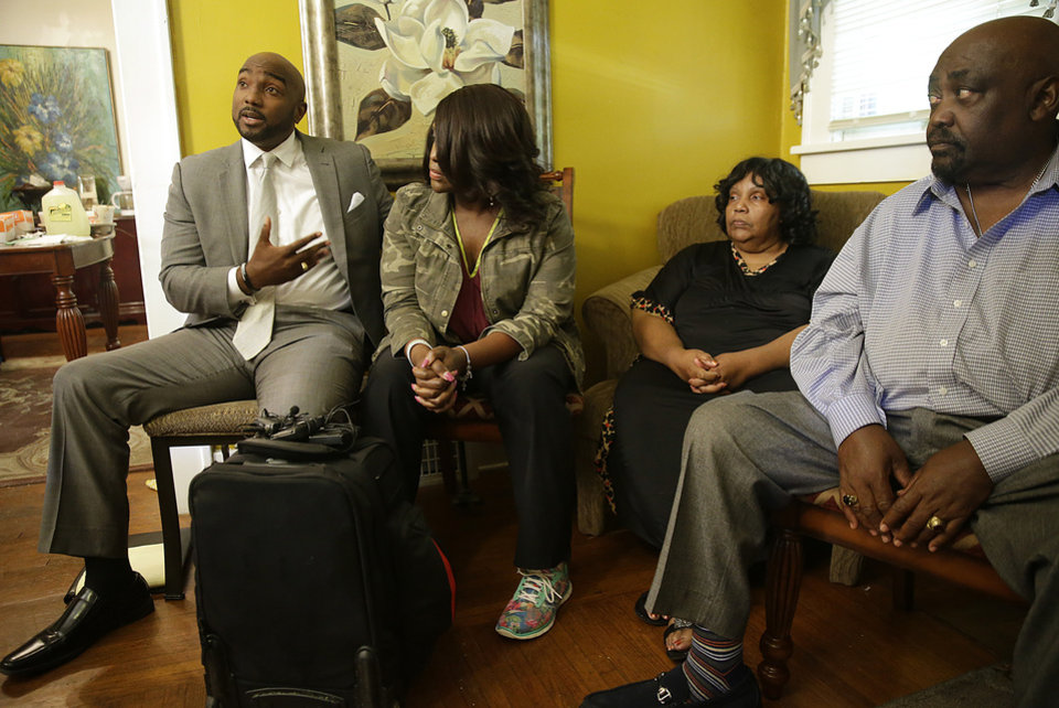 Photo - Attorney Damario Solomon-Simmons speaks as Tiffany Crutcher, twin sister of Terence Crutcher, Leanna Crutcher his mom and his father Rev. Joey Crutcher listen during a news conference at their home  Sept. 17, 2016.  Terence Crutcher was shot and killed by a Tulsa Police officer Friday night. MIKE SIMONS/Tulsa World
