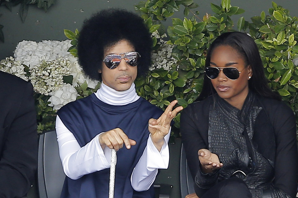 Photo - U.S. pop singer Prince, left, watches the fourth round match of the French Open tennis tournament between Spain's Rafael Nadal and Serbia's Dusan Lajovic at the Roland Garros stadium, in Paris, France, Monday, June 2, 2014. (AP Photo/Michel Spingler)