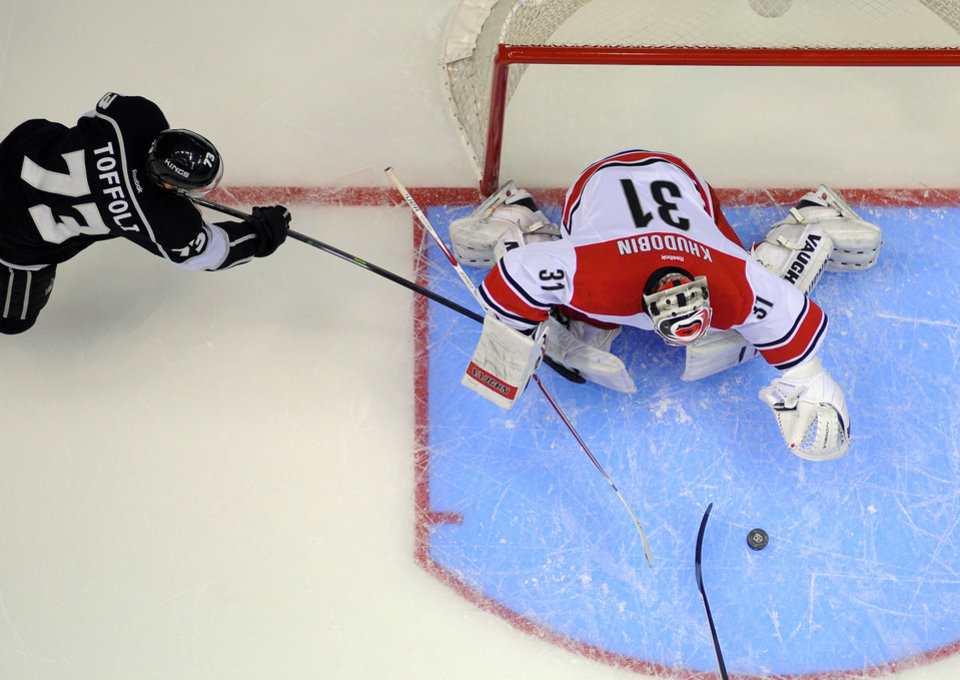 Photo - Los Angeles Kings center Tyler Toffoli, left, tries to get a shot in on Carolina Hurricanes goalie Anton Khudobin, of Kazakhstan, during the first period of an NHL hockey game, Saturday, March 1, 2014, in Los Angeles. (AP Photo/Mark J. Terrill)