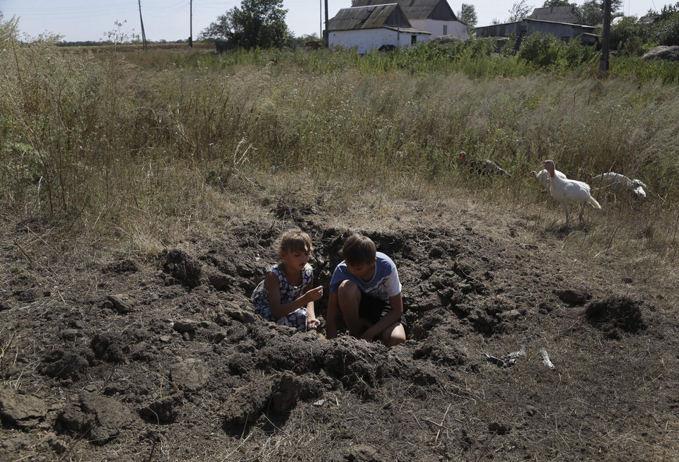Photo - Ksenia Plyushch, 7, and her brother Andrei, 10, collect pieces of shrapnel, as they play in shell crater in the village of Osykove, eastern Ukraine, Tuesday, Sept. 2, 2014. Ukrainian troops have over the past week suffered a string of major military losses in their offensive against Russian-backed separatist rebels, losing large swathes of territory and having hundreds of soldiers captured. (AP Photo/Sergei Grits)
