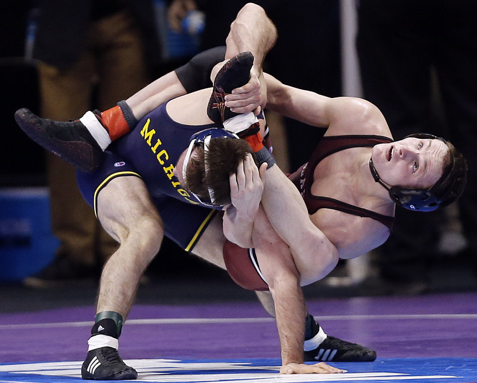 Photo - Oklahoma's Nick Lester takes on Michigan's Stephen Dutton III in the 141 pound match during the 2014 NCAA Div. 1 Wrestling Championships at Chesapeake Energy Arena in Oklahoma City, Okla. on Friday, March 21, 2014. Photo by Chris Landsberger, The Oklahoman