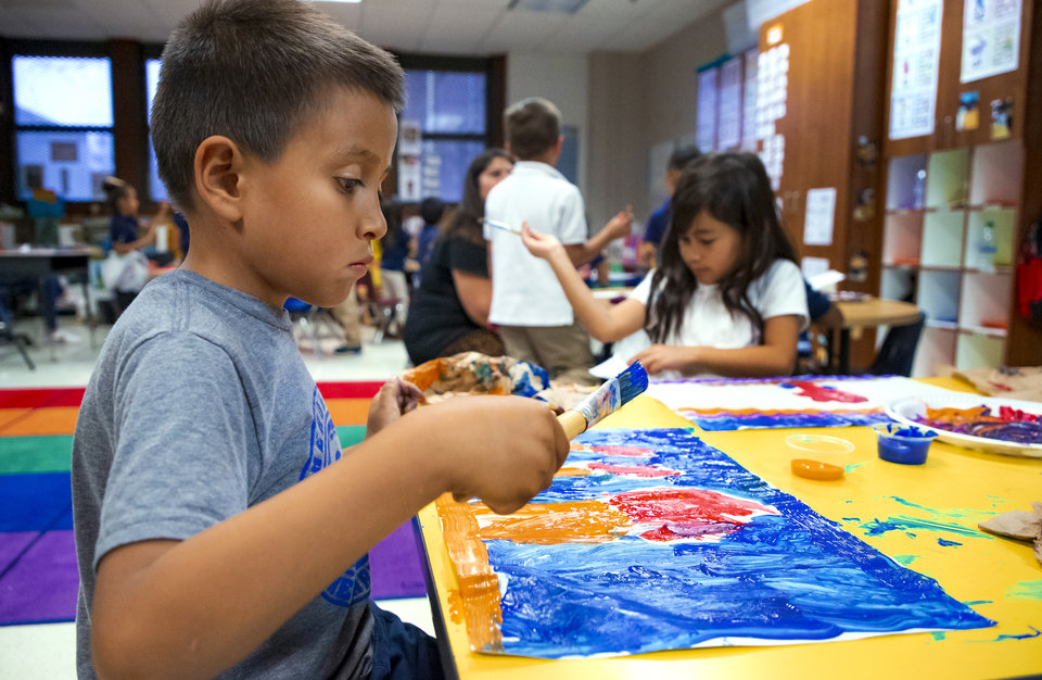Photo - Heronville Elementary first grader Jorge Rangel paints his view of a lesson on the story of Thanksgiving from the Native American perspective while in Alicia Strawn's class at Heronville Elementary in Oklahoma City, Okla. on Thursday, Nov. 21, 2019. [Chris Landsberger/The Oklahoman]