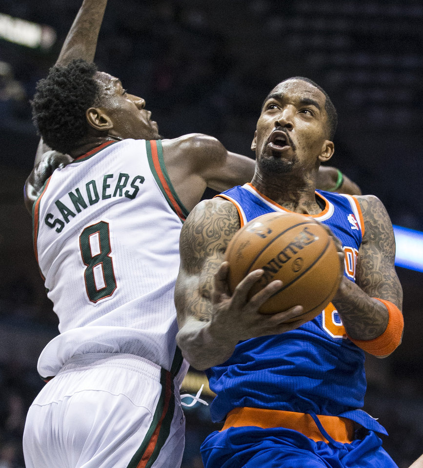 Photo - New York Knicks' J.R. Smith drives past Milwaukee Bucks' Larry Sanders for a shot during the first half of an NBA basketball game, Monday, Feb. 3, 2014, in Milwaukee. (AP Photo/Tom Lynn)