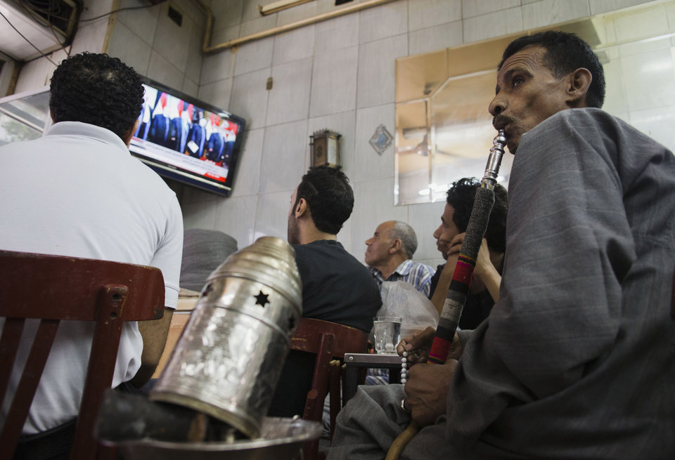 Photo - People gather in a tea shop to watch a state television broadcast as President Abdel-Fattah el-Sissi takes the oath of office, in the Zamalek district of Cairo, Egypt, Egypt, Sunday, June 8, 2014. El-Sissi was sworn in on Sunday as president for a four-year term, taking the reins of power in a nation roiled since 2011 by deadly unrest and economic woes. (AP Photo/Hiro Komae))