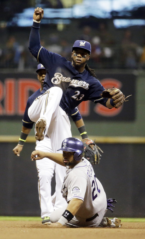 Photo - Colorado Rockies' Wilin Rosario (20) is out at second as Milwaukee Brewers' Rickie Weeks turns a double play on a ball hit by Vinny Castilla during the sixth inning of a baseball game Thursday, June 26, 2014, in Milwaukee. (AP Photo/Morry Gash)