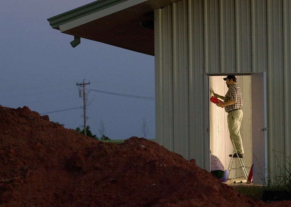 Photo - A volunteer puts a top coat on a wall of Ridgecrest Baptist Church in Bridge Creek during efforts in 2000 to rebuild the church building that was destroyed by a tornado on May 3, 1999.  BRYAN TERRY