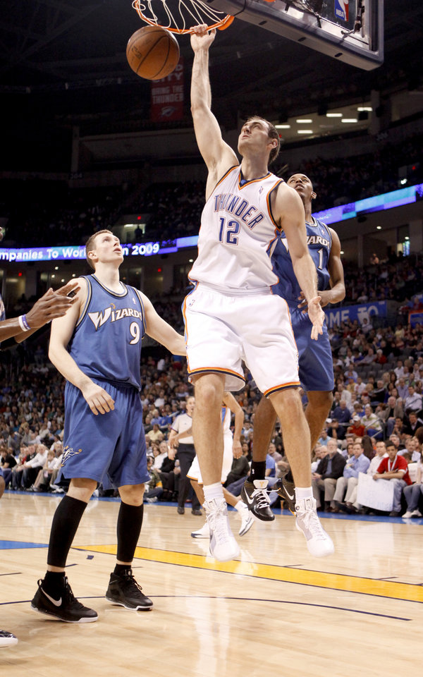 Photo - Oklahoma City's Nenad Krstic dunks the ball between Washington's Darius Songaila, left, and Nick Young during the NBA basketball game between the Oklahoma City Thunder and the Washington Wizards at the Ford Center in Oklahoma City, Wed., March 4, 2009. PHOTO BY BRYAN TERRY, THE OKLAHOMAN