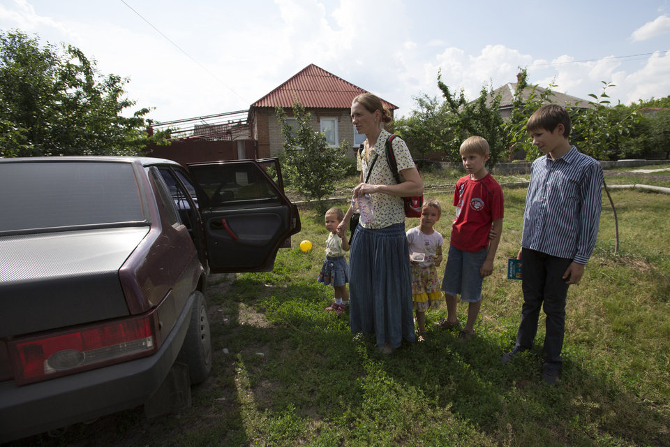 Photo - Olga Mikhailova, second left, prepares their children before abandoning their home in the town in Slovyansk, Ukraine, Wednesday, May 28, 2014.  In Slovyansk, a city 90 kilometers (55 miles) north of Donetsk which has seen repeated clashes over the past few weeks, with residential areas coming under mortar attack Wednesday from government forces. A school was badly damaged and other buildings were hit, according to residents, Wednesday, who told The Associated Press that several people were wounded.(AP Photo/Alexander Zemlianichenko)