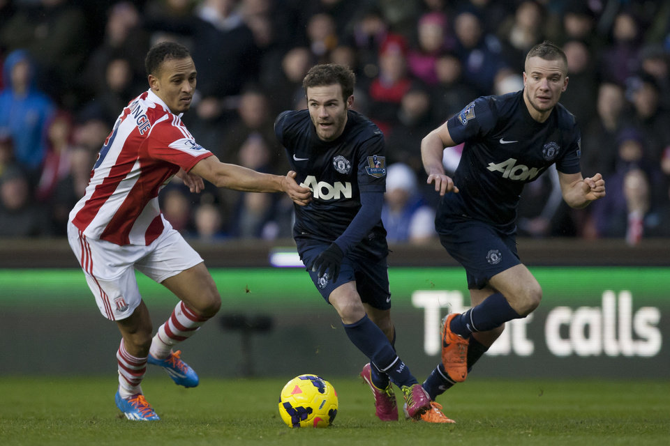 Photo - Manchester United's Juan Mata, centre, avoids the attentions of Stoke's  Peter Odemwingie, left, as Tom Cleverley looks on during their English Premier League soccer match at the Britannia Stadium, Stoke, England, Saturday Feb. 1, 2014. (AP Photo/Jon Super)