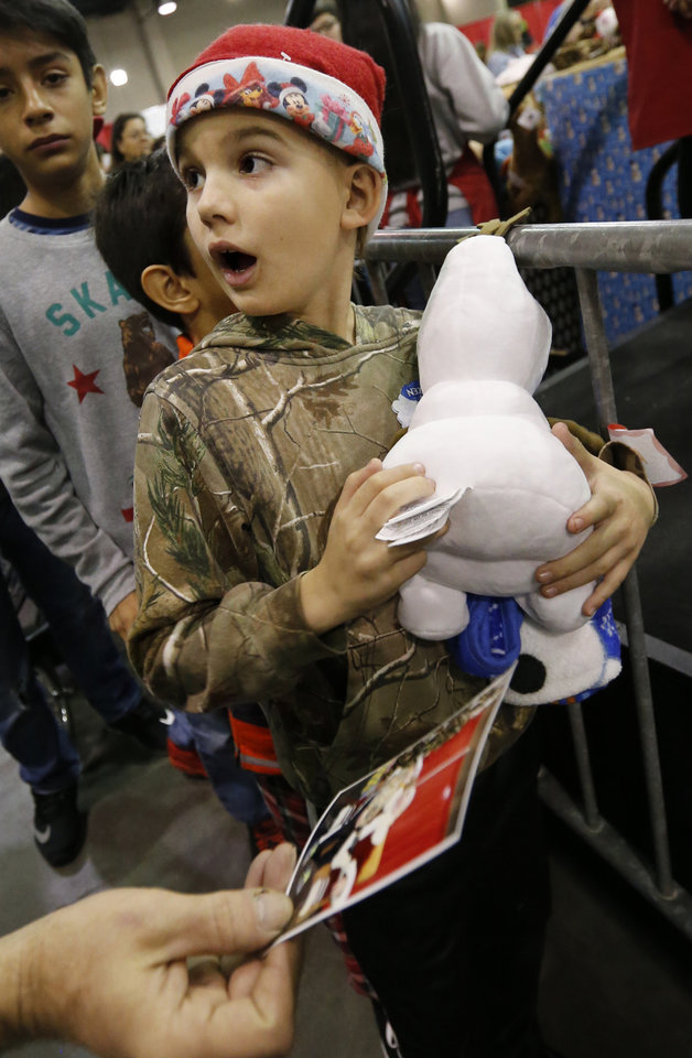 Photo -  Yelko Zablatnik, 9, reacts to getting a photo of his visit with Santa. [Photo by Steve Sisney, The Oklahoman]