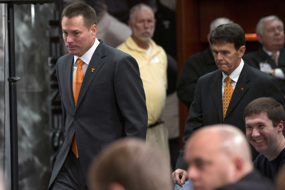 Photo - Tennessee football coach Butch Jones, left, arrives for a news conference with athletic director Dave Hart on Friday, Dec. 7, 2012, in Knoxville, Tenn. The former Cincinnati coach replaces Derek Dooley, who was fired on Nov. 18 after three losing seasons. (AP Photo/Adam Brimer, Knoxville News Sentinel)