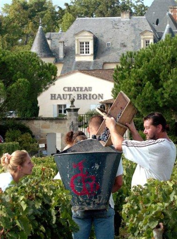 FILE - In this Sept. 19, 2006, file photo, workers collect red grapes in the vineyards of the famed Chateau Haut Brion, a Premier Grand Cru de Graves, during the grape harvest in Pessac-Leognan, near Bordeaux, southwestern France. Drinking a Bordeaux from a ''chateau'' is as French as apple pie is American. Now, Gallic tempers are flaring since the United States wants to sell some of their wines in the European Union with _ sacrilege _ a ''chateau'' label. Next week, EU experts will look whether it should permitted with a fight among member states set for later this year, well after the wine harvest. (AP Photo/Bob Edme, File)