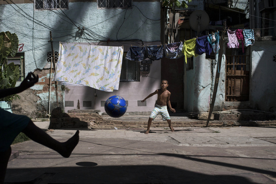 Photo - Igor Meireles, 8, center, plays goalkeeper as he prepares to block a kick from his brother Iago Meireles, 10, during their soccer game in the small square next to their home in Rio de Janeiro, Brazil, Sunday, March 16, 2014. The brothers took turns being the goalkeeper because neither wanted to play that position. With so many outstanding strikers and midfielders in Brazilian history, few chose goalkeepers as their childhood idols. (AP Photo/Felipe Dana)