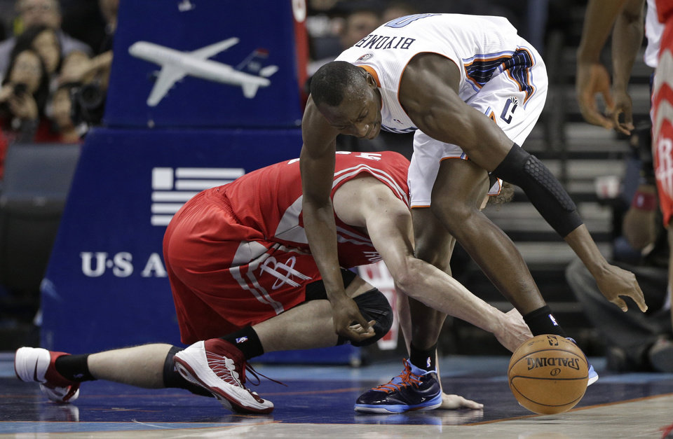 Charlotte Bobcats' Bismack Biyombo, top, and Houston Rockets' Omer Asik, bottom, chase a loose ball during the first half of an NBA basketball game in Charlotte, N.C., Monday, Jan. 21, 2013. (AP Photo/Chuck Burton)
