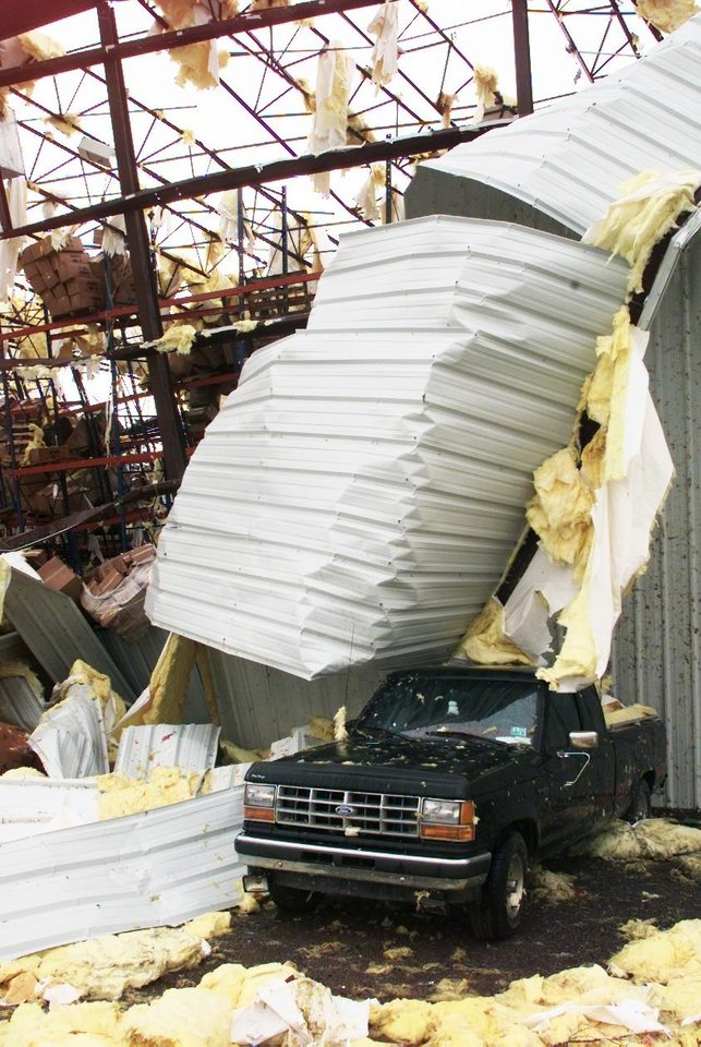 MAY 3, 1999 TORNADO: The roof of the Sygma food distribution center near Stroud covers a vehicle parked at the side of the building.