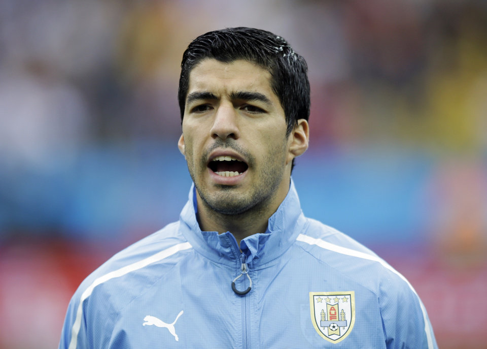 Photo - Uruguay's Luis Suarez sings the national anthem before the group D World Cup soccer match between Uruguay and England at the Itaquerao Stadium in Sao Paulo, Brazil, Thursday, June 19, 2014.  (AP Photo/Matt Dunham)