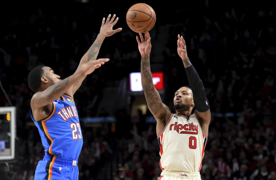 Photo - Portland Trail Blazers guard Damian Lillard, right, hits a shot over Oklahoma City Thunder guard Terrance Ferguson during the second half of an NBA basketball game in Portland, Ore., Wednesday, Nov. 27, 2019. The Blazers won 136-119. (AP Photo/Steve Dykes)