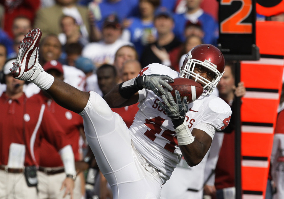 Photo - Oklahoma defensive end Jeremy Beal (44) intercepts a pass by Kansas' Todd Reesing during the first half of their NCAA college football game Saturday, Oct. 24, 2009, in Lawrence, Kan. (AP Photo/Orlin Wagner)