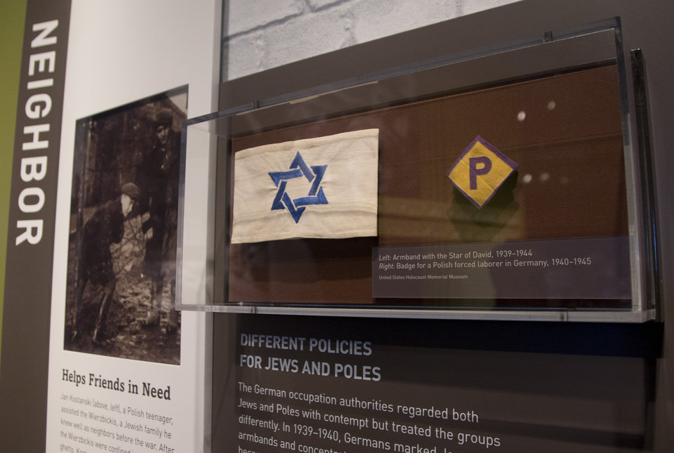 This Thursday, April 25, 2013 photo shows an armband with the Star of David and a badge for a forced laborer in Germany at the United States Holocaust Memorial Museum during a preview of the new exhibit