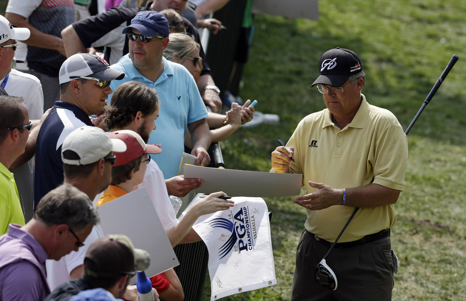 Photo - Kenny Perry signs autographs during a practice round for the PGA Championship golf tournament at Valhalla Golf Club on Wednesday, Aug. 6, 2014, in Louisville, Ky. The tournament is set to begin on Thursday. (AP Photo/John Locher)