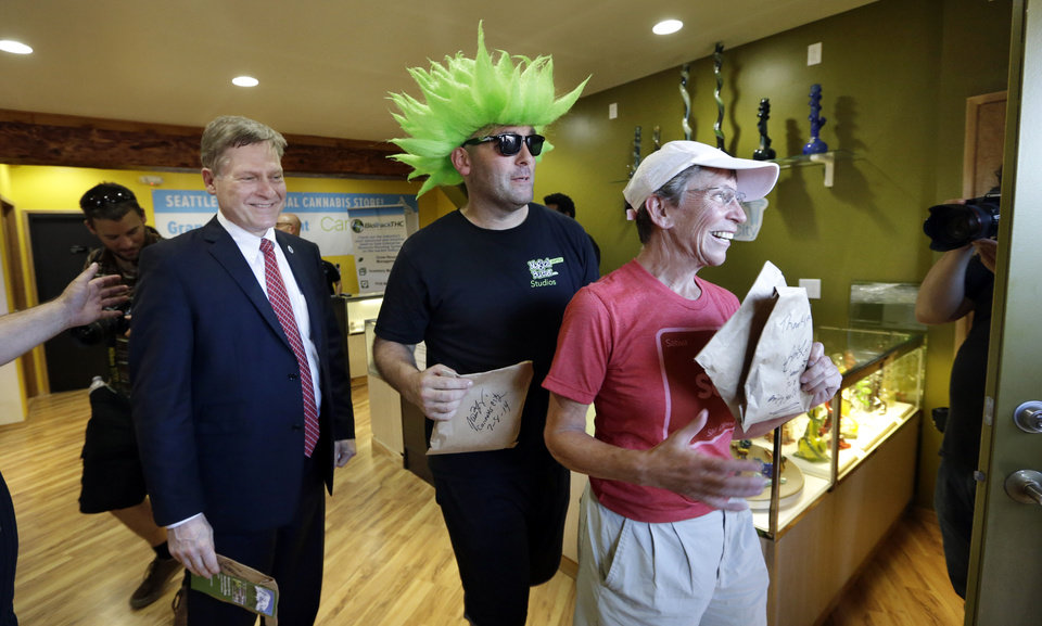 Photo - Seattle City Attorney Pete Holmes, left, Jeremy Cooper and Deb Greene walk out after being among the very first customers to legally purchase recreational pot in Seattle at Cannabis City, Tuesday, July 8, 2014.  Washington on Tuesday became the second state to allow people to buy marijuana legally in the U.S. without a doctor's note as eager customers who lined up outside stores made their purchases and savored the moment. (AP Photo/Elaine Thompson, Pool)
